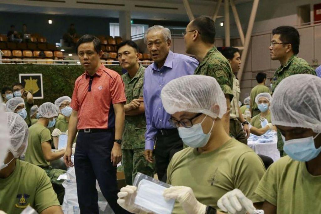 BERSAMA ATASI WABAK: Menteri Pertahanan Dr Ng Eng Hen (berbaju biru) dan Menteri Perdagangan dan Perusahaan Chan Chun Sing (berbaju merah) meninjau pembungkusan pelitup oleh anggota Angkatan Bersenjata Singapura (SAF) pada 31 Januari 2020.