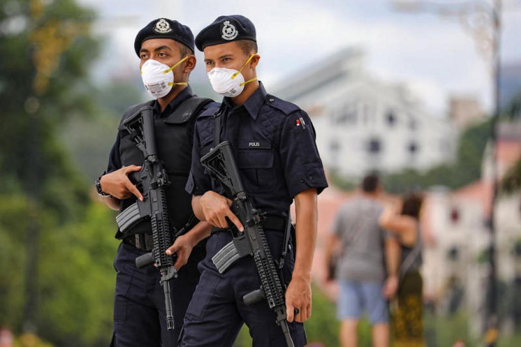 Pegawai polis Malaysia menggunakan pelitup muka semasa menjalankan tugas berikutan wabak koronavirus COVID-19. FOTO: REUTERS
