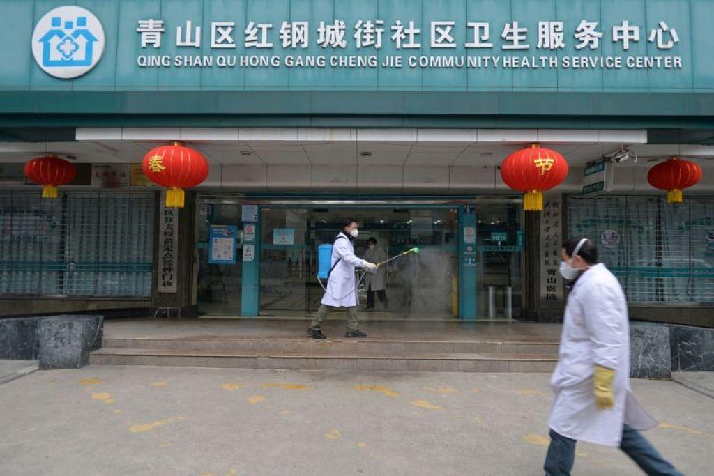 BERSIHKAN: Pekerja perubatan membersihkan pintu masuk sebuah kemudahan penjagaan kesihatan di Wuhan, China pada 2 Februari 2020.