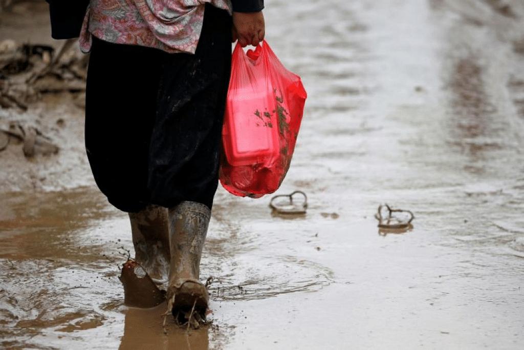 Seorang wanita membawa beg plastik mengandungi makanan di Bekasi, wilayah Jawa Timur, Indonesia. - Foto REUTERS