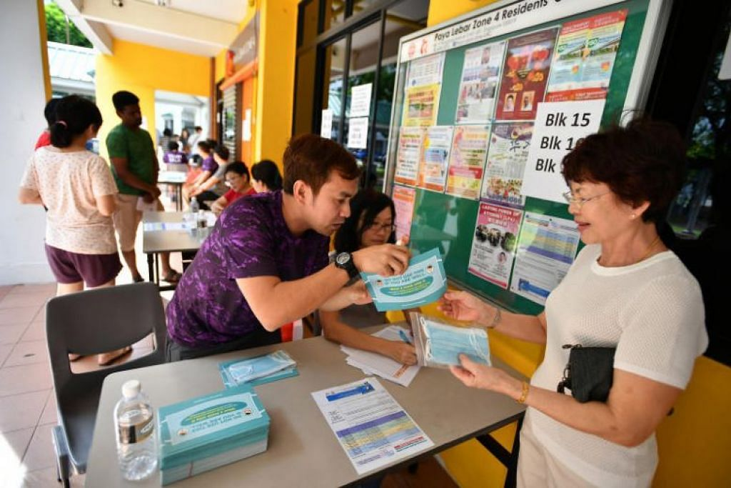 Soerang wanita sedang menerima pelitup percuma di Hougang pada 1 Februari 2020. - Foto: Lim Yaohui