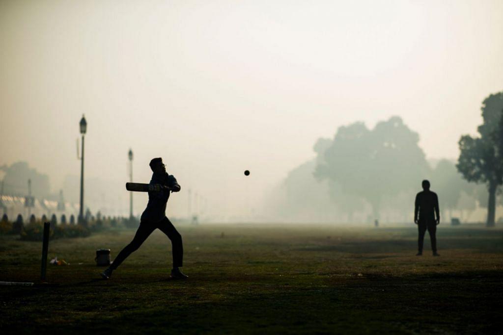 UDARA TERCEMAR: Belia bermain kriket di taman dalam keadaan udara berasbut di New Delhi pada 17 Februari lalu. – Foto AFP