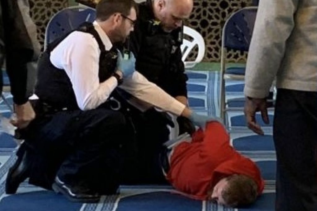 Gambar yang diterbitkan di Twitter menunjukkan pegawai polis menahan seorang lelaki di dewan sembahyang sebuah masjid di London.