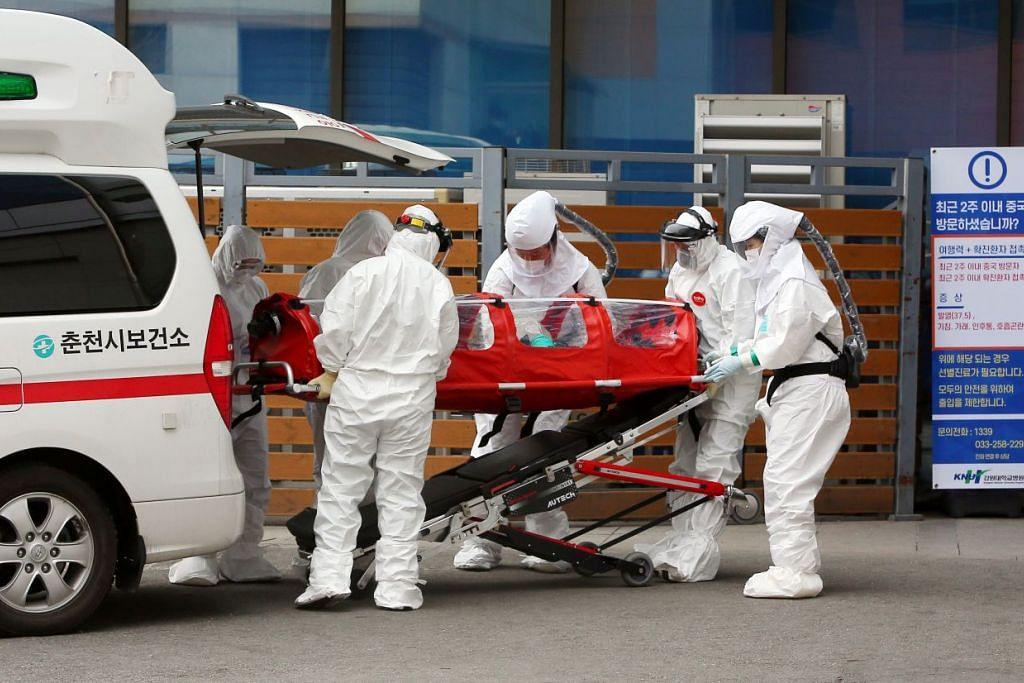 Pekerja kesihatan yang dilihat memakai alat pelindung sambil menolak seorang pesakit di sebuah hospital di Chuncheon, Korea Selatan pada 22 Februari 2020. - Foto: AFP.