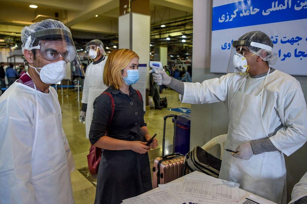 Beberapa kakitangan lapangan terbang memantau suhu badan seorang penumpang pesawat di lapangan terbang Hamid Karzai, Kabul, Afghanistan pada 2 Februari 2020. - Foto: AFP
