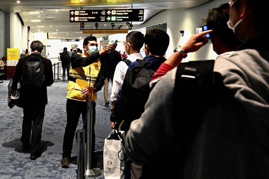 Seorang pegawai kesihatan Indonesia memantau suhu badan beberapa penumpang pesawat setibanya mereka di Lapangan Terbang antarabangsa Jakarta pada 23 Februari 2020. - Foto: AFP