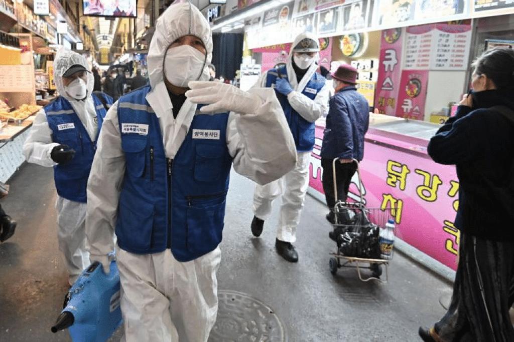 Kakitangan Persatuan Kawalan Perosak Korea, memakai pakaian perlindungan, memyembur ubat kuman untuk bantu mencegah penularan koronavirus di sebuah pasar di Seoul. - Foto AFP