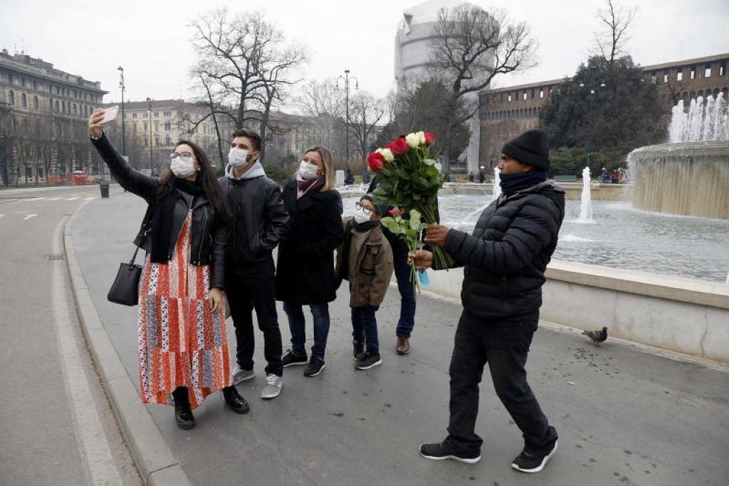 Sebuah keluarga memakai pelitup muka bergambar di Sforza Castle di Milan, Italy pada Selasa (25 February).