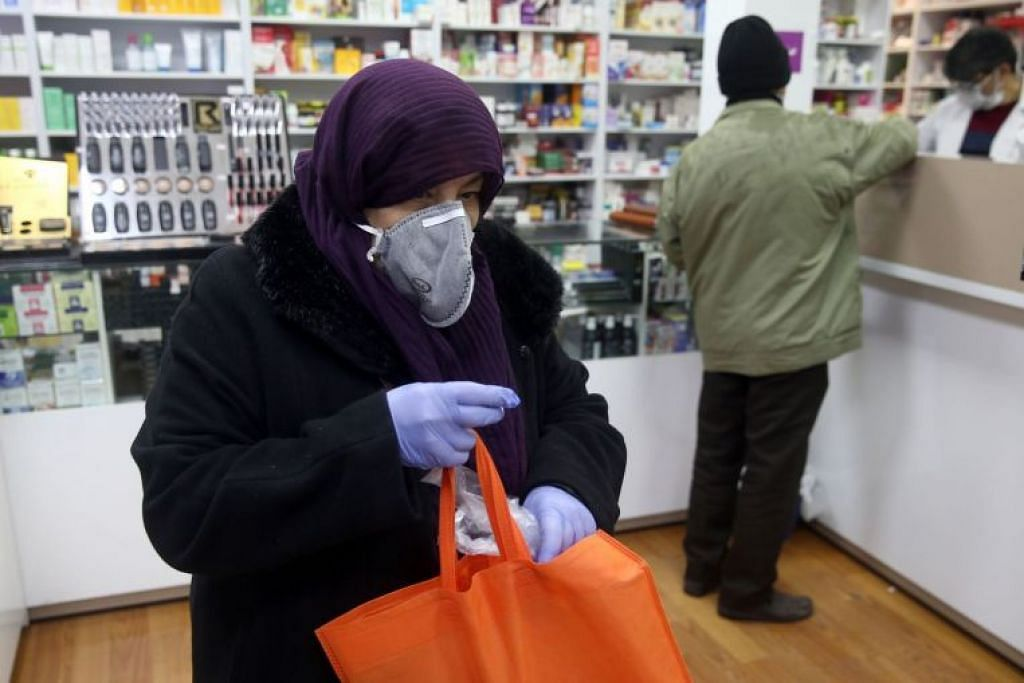 Seorang wanita memakai pelitup muka ketika mengunjungi kedai ubat di Teheran, Iran pada Selasa (25 Februari).