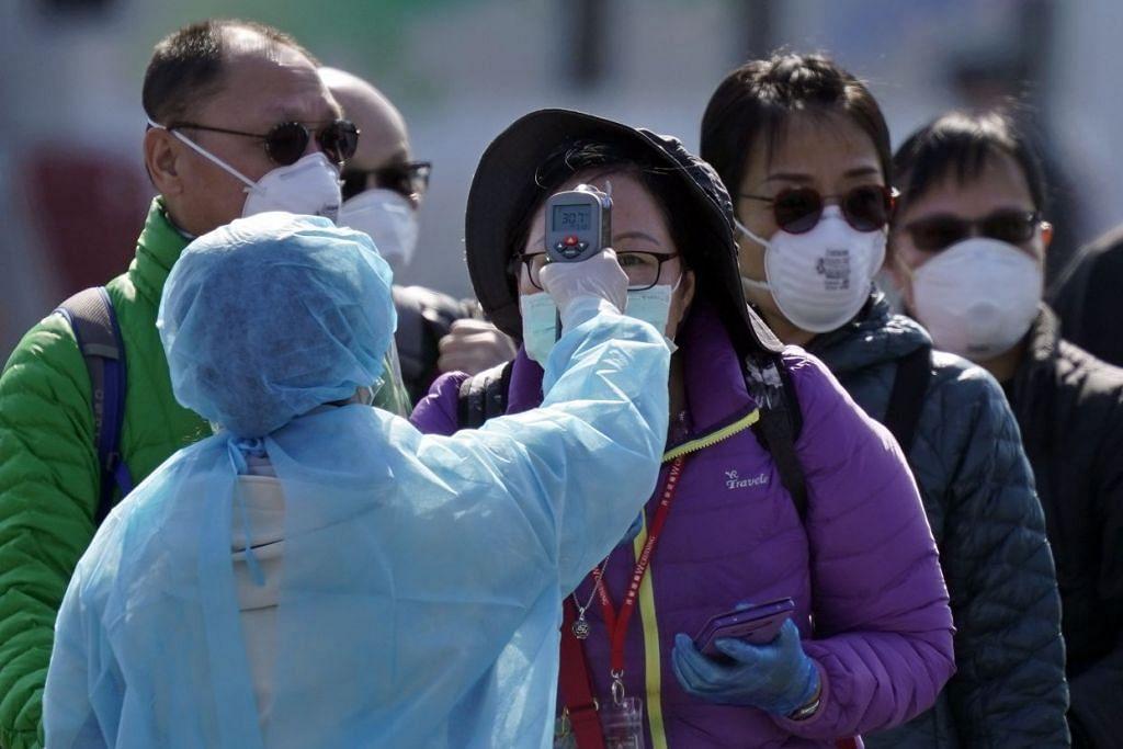 Seorang pekerja kesihatan dilihat sedang memantau suhu badan para penumpang kapal pesiaran Diamond Pricess di Yokohama pada 21 Februari 2020. Foto: EPA-EFE