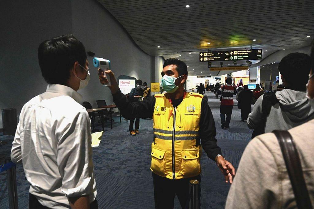 Pekerja kesihatan memantau suhu badan penumpang pesawat di Lapangan Terbang antarabangsa Jakarta. Foto: AFP.