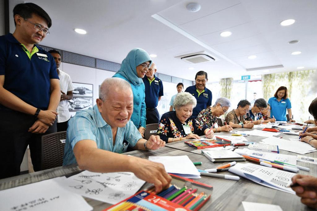Presiden Halimah Yacob berinteraksi dengan warga tua yang menulis poskad bagi kakitangan penjagaan perubatan di Pusat Penjagaan Warga Tua St Luke's (Ayer Rajah) pada 26 Februari lalu. - Foto LIM YAOHUI