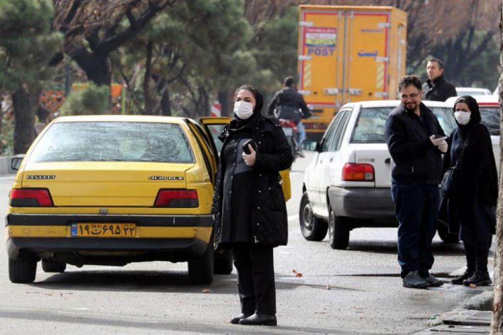 Orang ramai dilihat memakai pelitup muka semasa menunggu teksi di Tehran pada 26 Februari lalu.