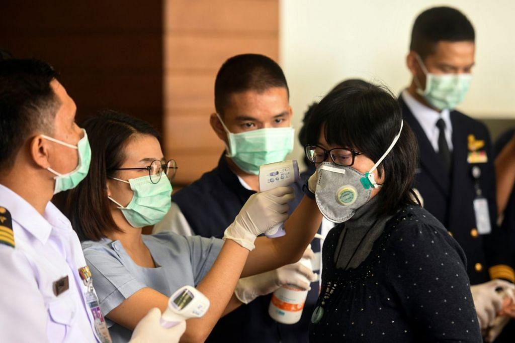 Seorang pegawai kesihatan memeriksa suhu badan di Lapangan Terbang, Don Mueang, Thailand. Foto: REUTERS