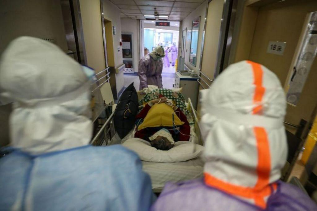 Kakitangan perubahan memindahkan seorang pesakit dijangkiti Covid-19 di sebuah hospital Palang Merah di Wuhan pada 28 Februari.