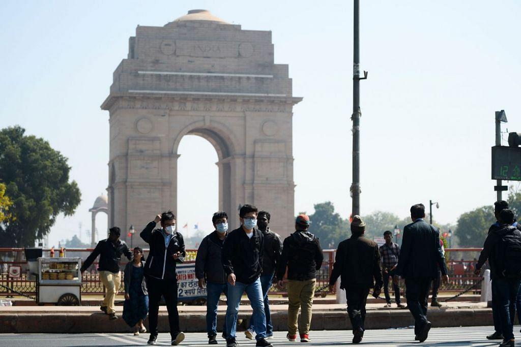 Beberapa pelancong dilihat memakai pelitup berdekatan dengan Gerbang India, New Delhi, India pada 13 Februari 2020. - Foto: AFP