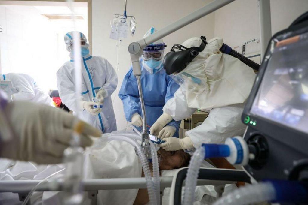 Kakitangan perubatan sedang merawat pesakit dijangkiti koronavirus di sebuah hospital Palang Merah di Wuhan pada 1 Mac.