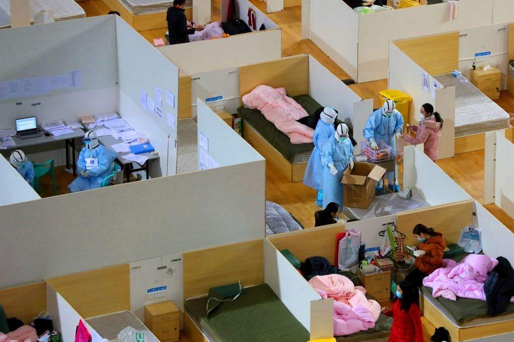 Pekerja kesihatan dilihat sedang mengagihkan makanan kepada pesakit di satu stadium yang diubah menjadi hospital sementara di Wuhan pada 2 Mac 2020. Foto: REUTERS