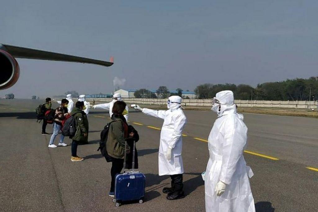 PERIKSA PENUMPANG: Pegawai lapangan terbang New Delhi menjalankan pemeriksaan suhu ke atas penumpang yang tiba dari Wuhan pada 2 Februari lalu. India kini juga memeriksa penumpang dari Singapura dan Thailand.