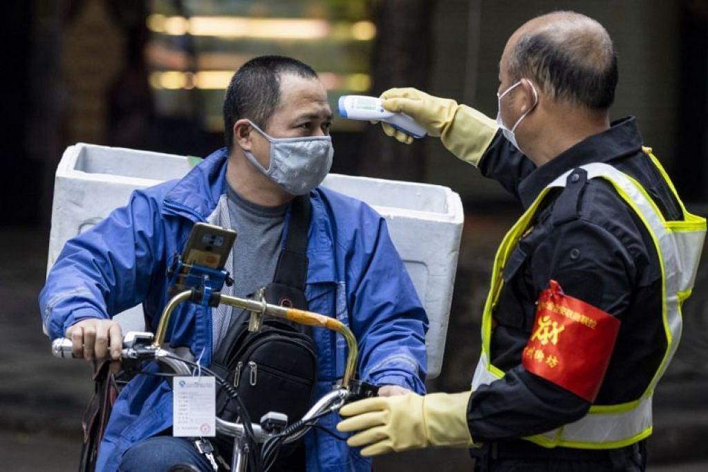 AMBIL SUHU: Seorang pengawal keselamatan memeriksa suhu pengunjung di sebuah pasar di Guangzhou, China.
