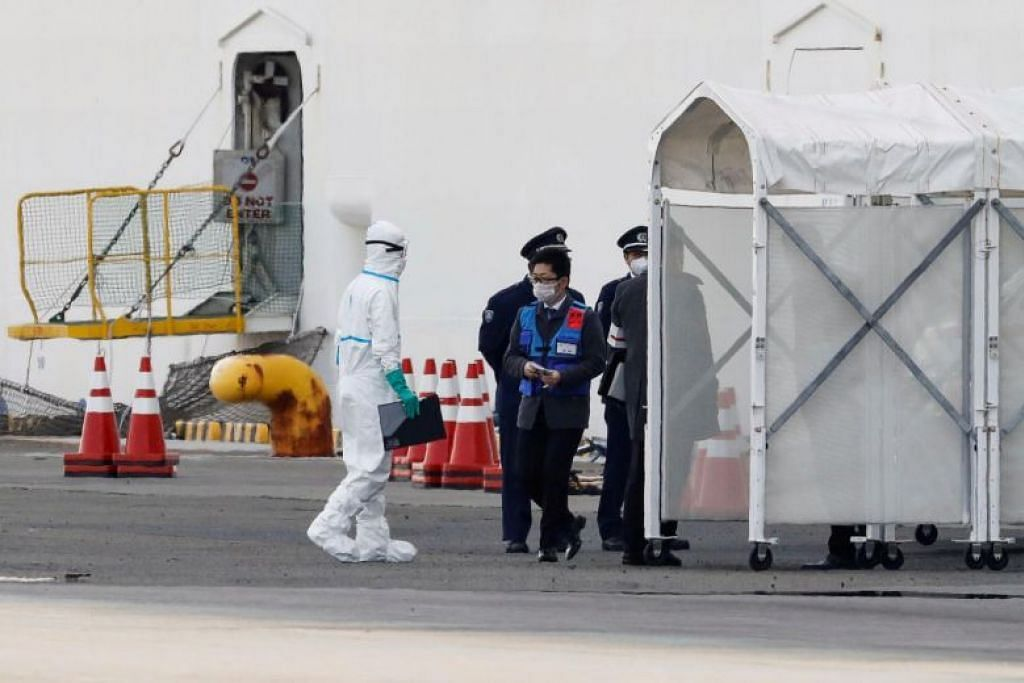 Pekerja menggunakan pakaian pelindung berdekatan kapal pelayaran Diamond Princess di Terminal Pelayaran Daikoku Pier di Yokohama, Jepun. FOTO: REUTERS