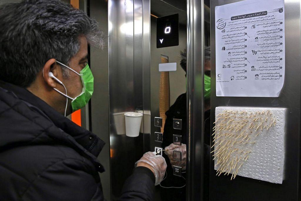 MENULAR SECARA MENDADAK: Seorang lelaki warga Iran menggunakan lidi untuk menekan butang lif dalam satu bangunan pejabat di Tehran, Iran pada 4 Mac 2020. - Foto: AFP