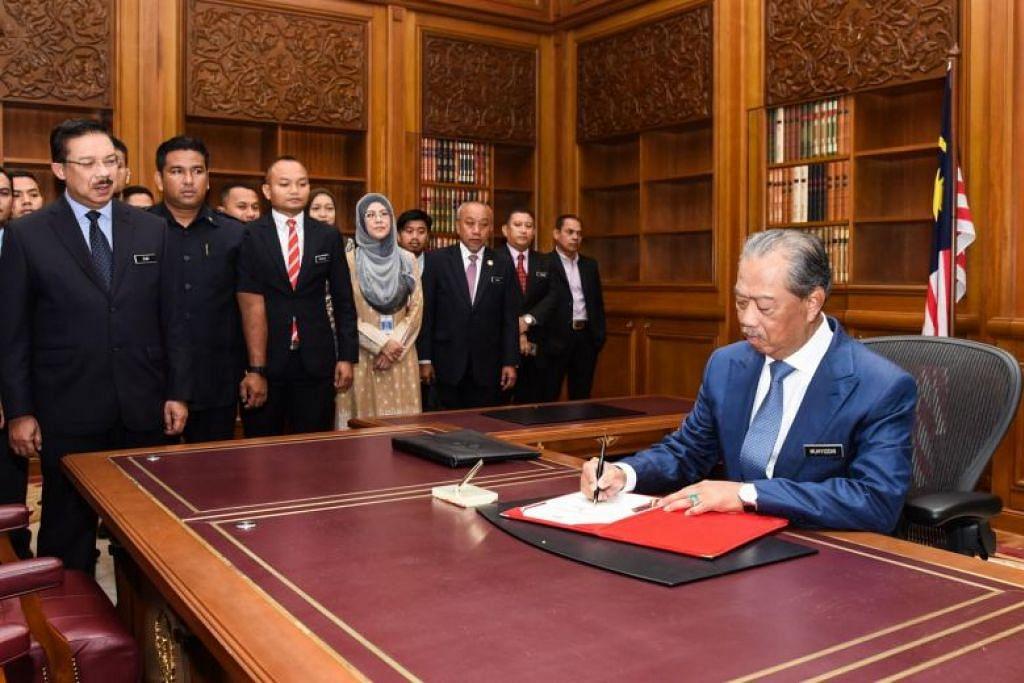 Perdana Menteri Tan Sri Muhyiddin Yassin menandatangani satu dokumen pada hari pertamanya di Pejabat Perdana Menteri di Putrajaya pada 2 Mac.