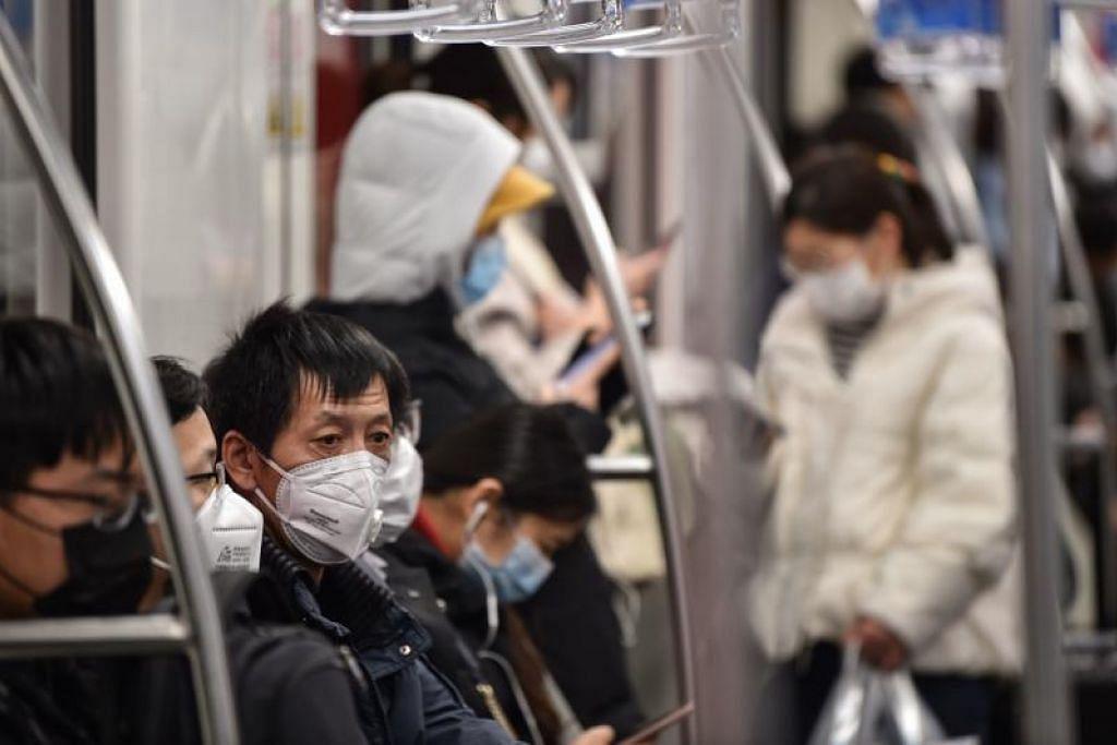 Warga China menggunakan pelitup dalam kereta api sedang Covid-19 masih menular. FOTO: AFP