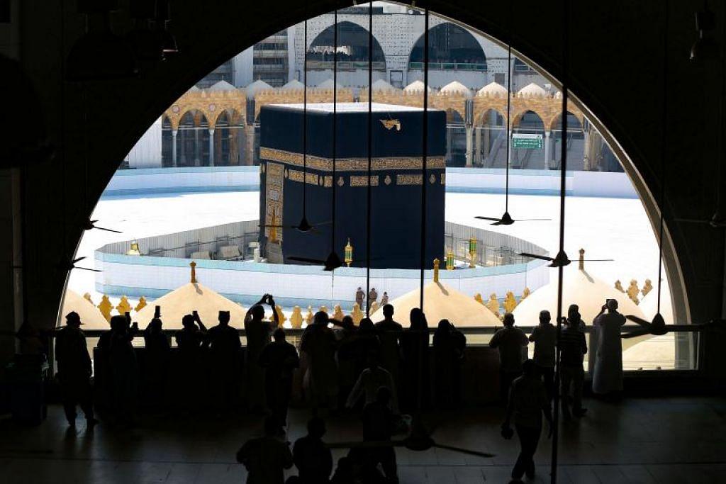 Jemaah mengambil gambar Kaabah dari dalam Masjidil Haram pada 6 Mac 2020, sehari selepas pihak Saudi menutup kawasan masjid itu bagi kerja pembersihan.