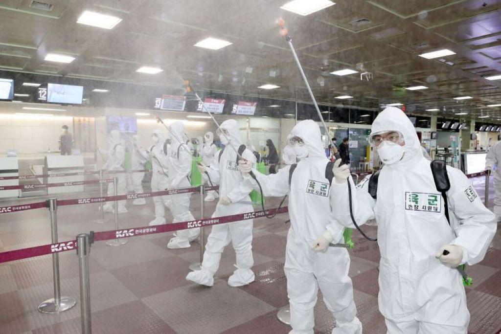 BASMI KUMAN: Tentera berpakaian sut perlindungan menyembur bahan basmi kuman di Lapangan Terbang Antarabangsa Daegu pada 6 Mac 2020.