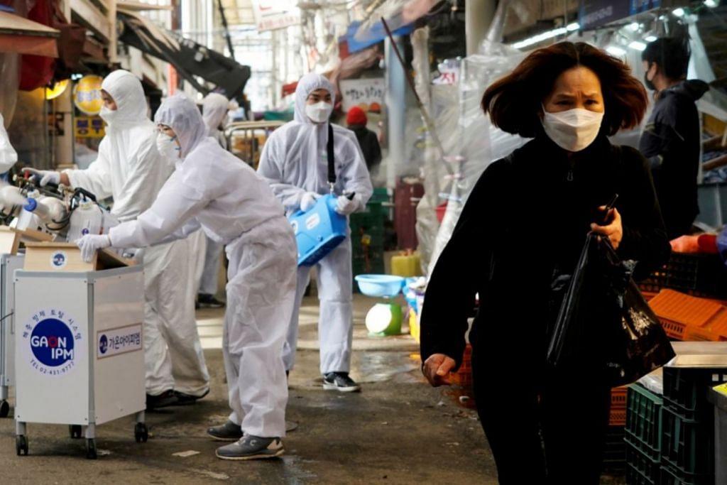 HAPUS VIRUS: Seorang wanita memakai pelitup di kawasan pasar tradisional di ibu kota Seoul sedang beberapa pekerja cuba mensanitasikan pasar itu. – Foto REUTERS