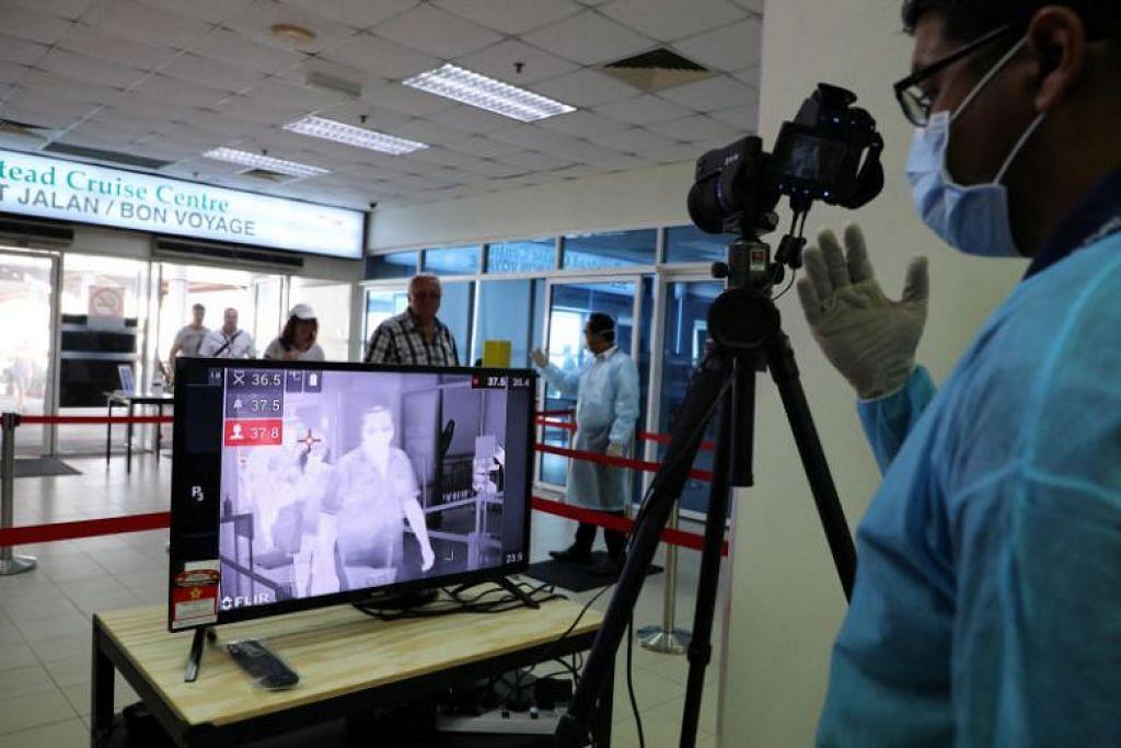 LANGKAH PENCEGAHAN: Seorang pegawai kuarantin kesihatan Malaysia di tempat pemeriksaan suhu di sebuah terminal kapal persiaran di Pelabuhan Klang pada 13 Februari 2020.