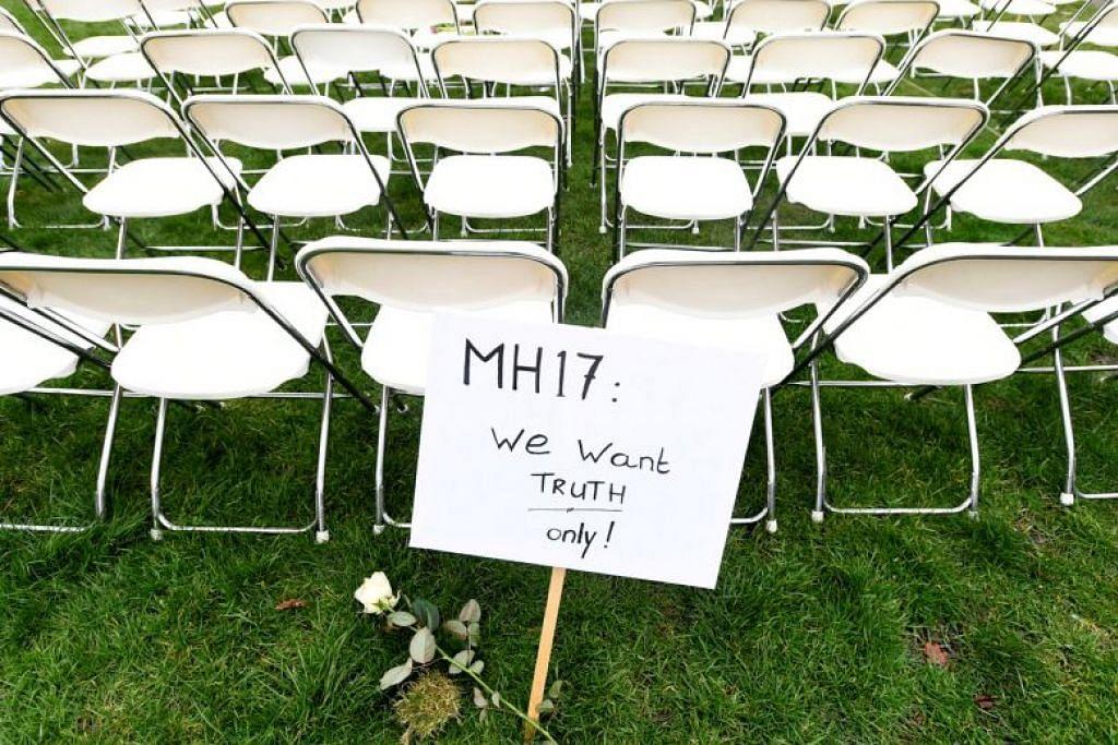 Satu tanda bantahan berhampiran deretan bangku sedang keluarga mangsa MH17 mengatur bangku kosong bagi setiap tempat duduk dalam pesawat dalam satu bantahan di luar Kedutaan russia di The Hague, Netherlands, pada 8 Mac.