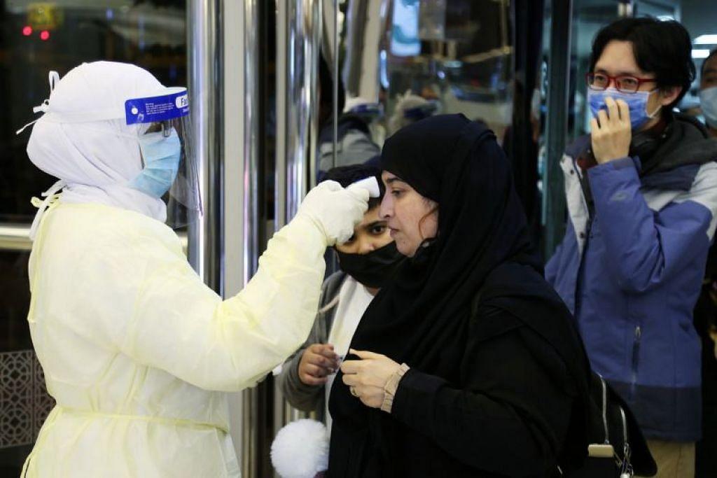 Kakitangan Kementerian Kesihatan Saudi memeriksa suhu badan penumpang setibanya di Lapangan Terbang Antarabangsa Raja Khalid di Riyadh, Arab Saudi pada 29 Januari.