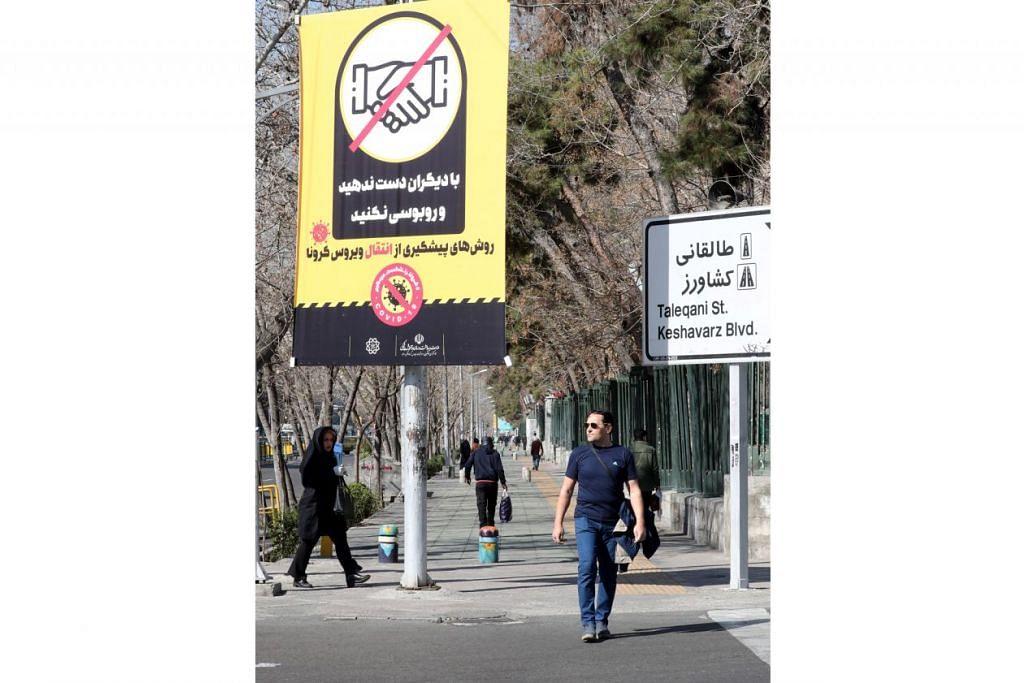 SEBAR MESEJ: Papan tanda di ibu kota Iran, Teheran, mengenai tingkah laku untuk mencegah penularan Covid-19, termasuk tidak bersalaman. – Foto EPA-EFE