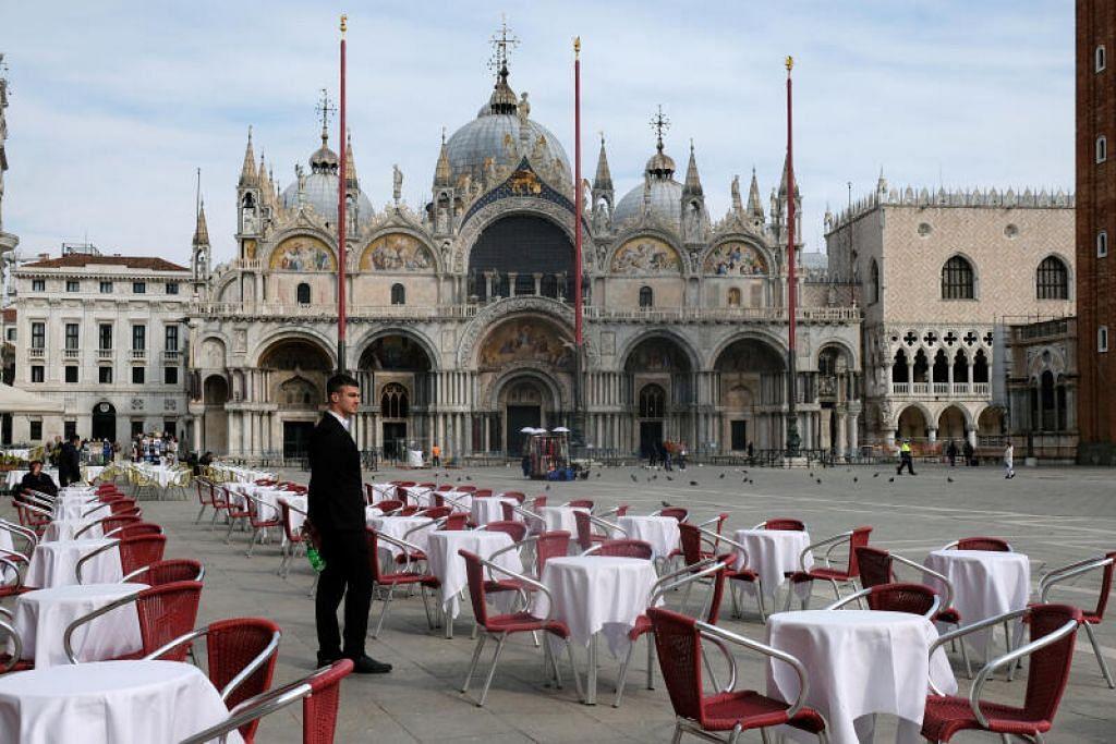 KOSONG: Seorang pelayan berdiri di tengah-tengah meja kosong di luar sebuah restoran di St Mark's Square setelah pemerintah mengenakan sekatan ke bahagian utara Italy, termasuk Venice.