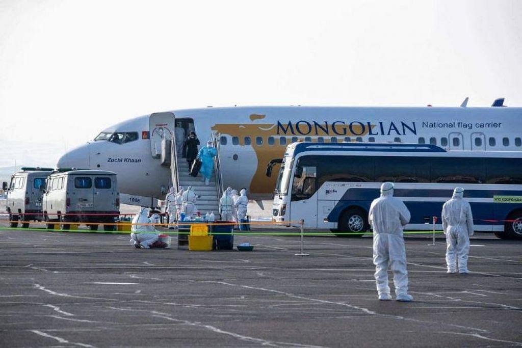 MONGOLIA BERDEPAN DENGAN COVID-19: Seorang warga Mongolia turun dari sebuah pesawat di Ulaanbaatar pada 1 Februari 2020 setelah berpindah keluar dari Wuhan. - Foto AFP