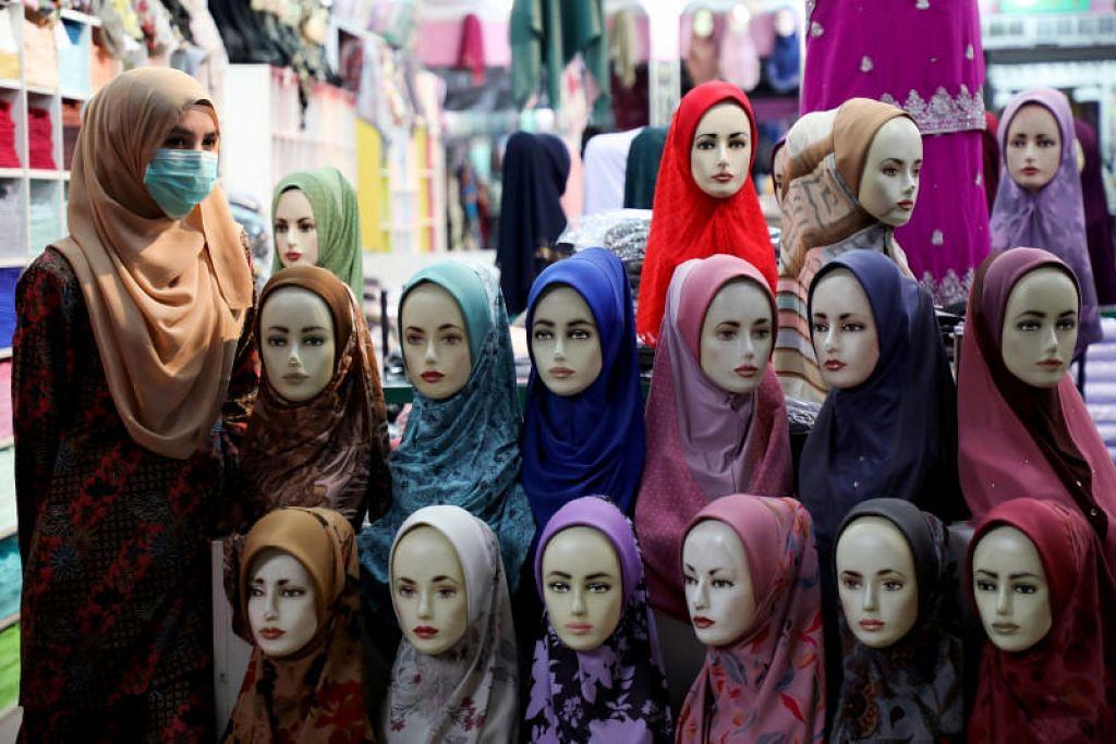 TUTUP MUKA: Seorang wanita memakai pelitup di kedai tudung di Kuala Lumpur pada 6 Mac 2020.