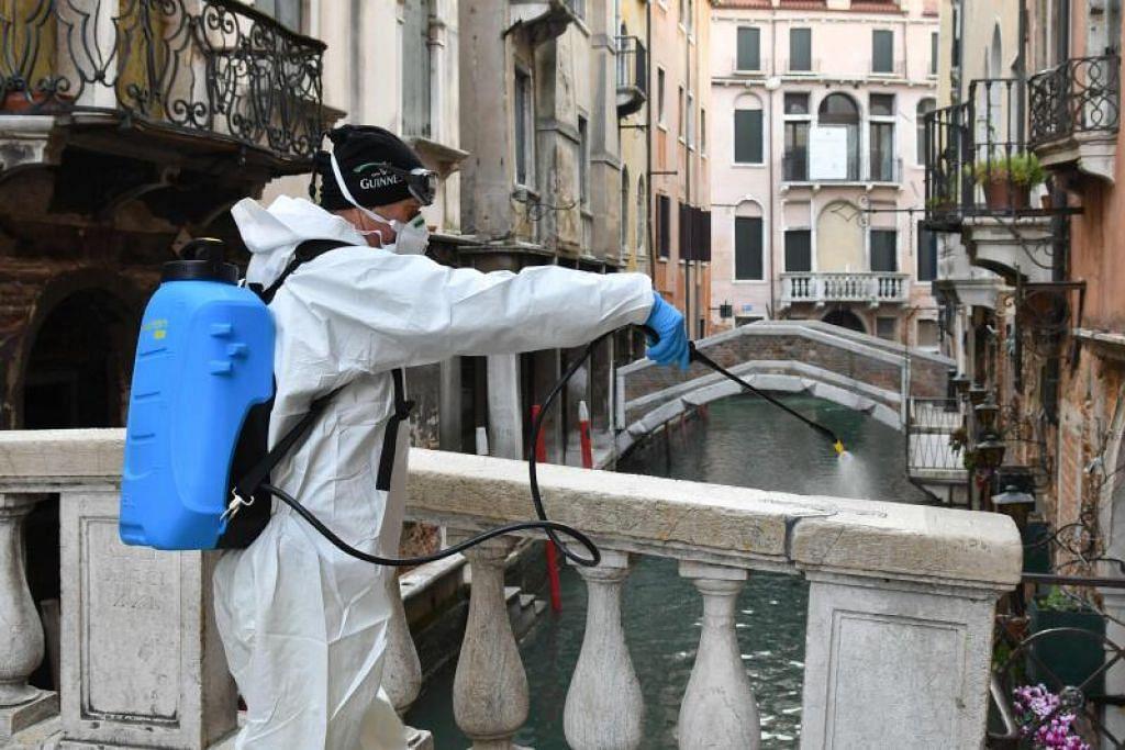 LANGKAH PENCEGAHAN: Seorang pekerja menyembur bahan penyahjangkit di Venice pada 11 Mac 2020 sebagai langkah pencegahan terhadap wabak koronavirus.