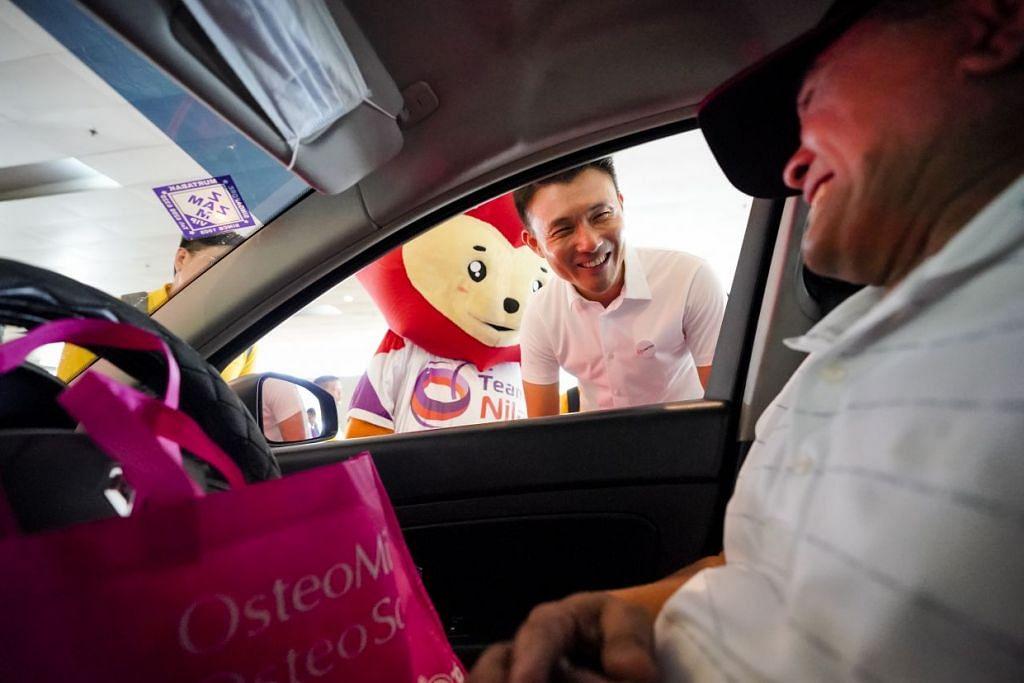 TUNJUK PRIHATIN: Encik Baey turut mengagih-agihkan pek habuan kepada pemandu teksi di Lapangan Terbang Changi.