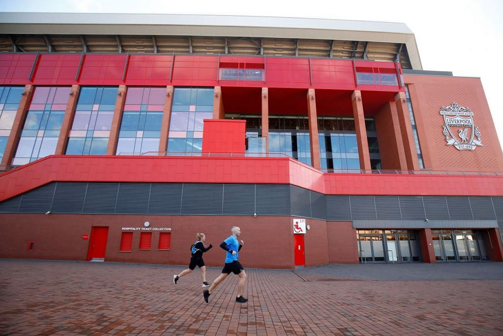 Dua orang berlari anak di luar Stadium Anfield di Liverpool pada 14 Mac. Perlawanan Liverpool dengan Crystal Palace pada hujung minggu ini telah digantung kepada tarikh selepas 3 April, seperti semua perlawanan Liga Perdana England yang lain.