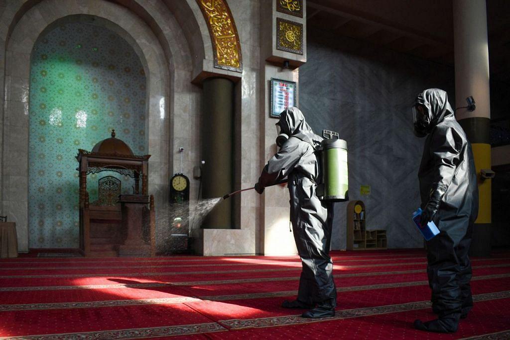 PERTINGKAT USAHA: Seorang pegawai pembersihan menyembur cecair pembasmi kuman di sebuah masjid di Bandung, Jawa Barat.