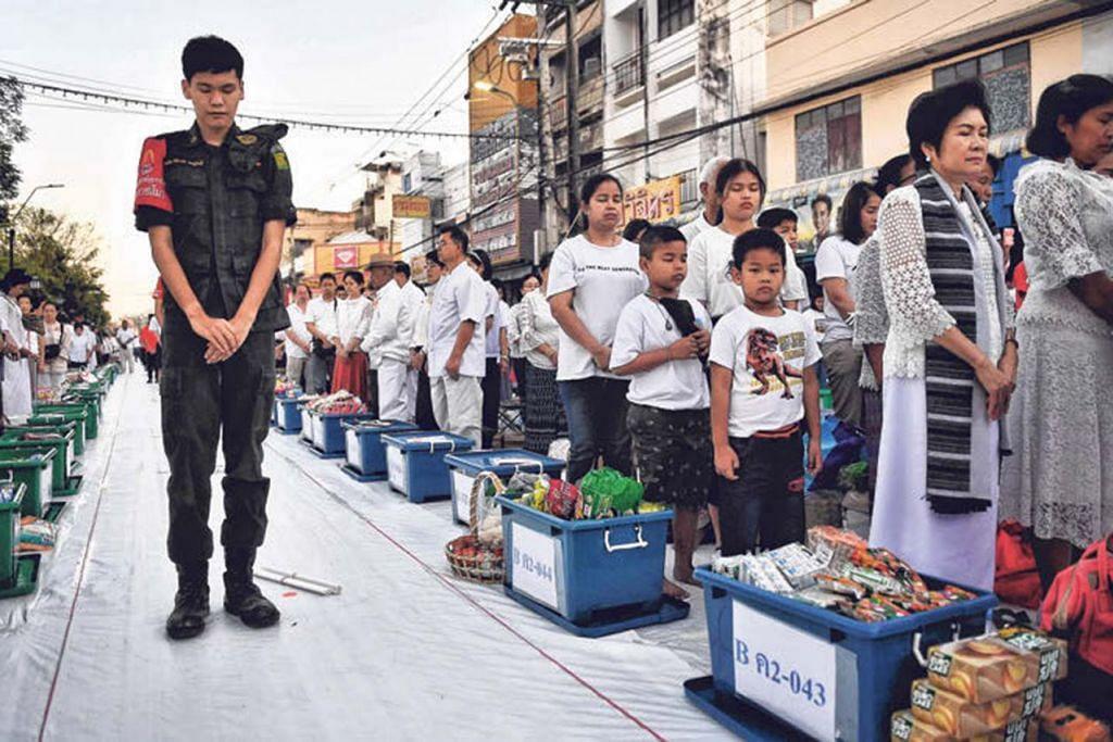 PERINGATI MANGSA: Orang ramai bertafakur sebagai memperingati 29 orang yang dibunuh seorang askar di wilayah Nakhon Ratchasima. - Foto AFP