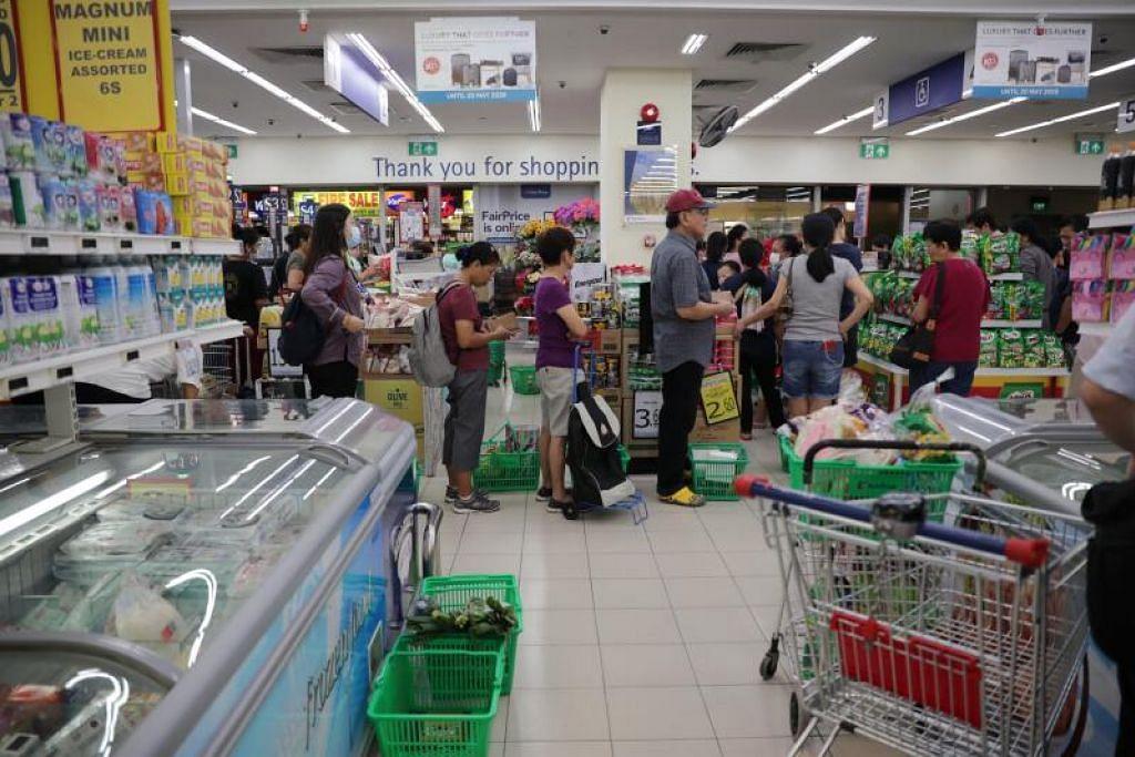 BELI BARANGAN KEPERLUAN: Orang ramai beratur di pasar raya FairPrice Toa Payoh Lorong 6 pada 17 Mac 2020, sehari selepas Malaysia mengumumkan perintah kawalan pergerakan selama dua minggu di negara itu.