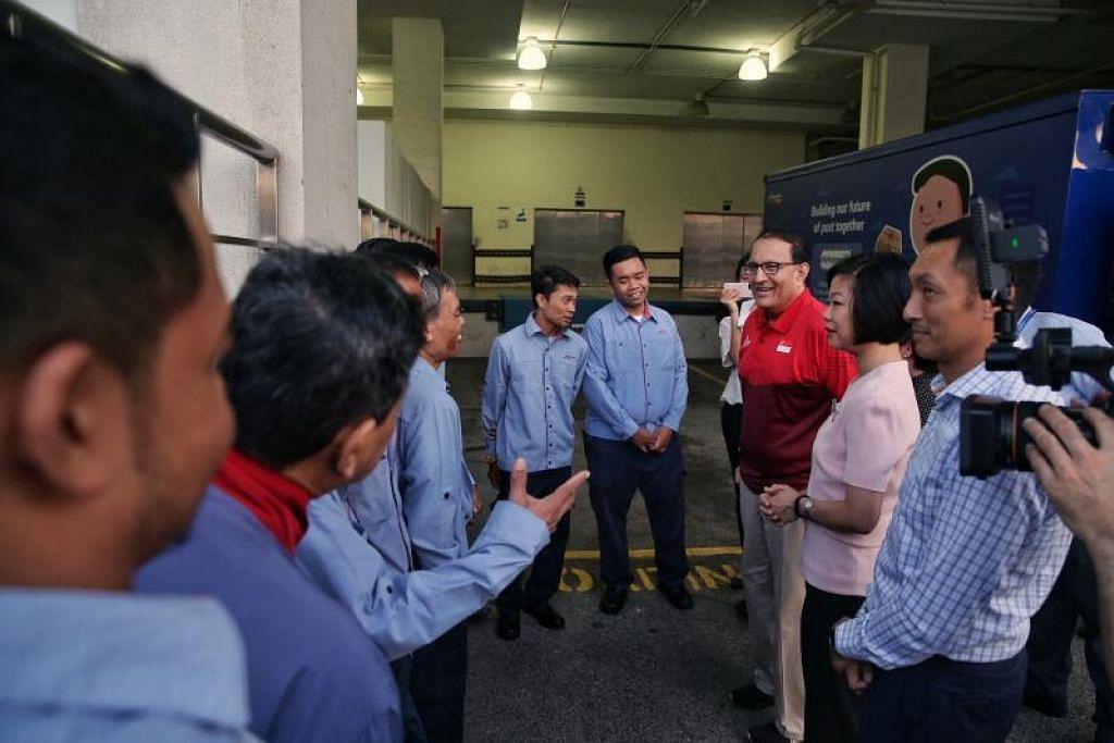 LAHIR PENGHARGAAN: Menteri Perhubungan dan Penerangan S. Iswaran dan Menteri Kanan Sim Ann (tiga dan dua dari kanan) mengunjungi kemudahan SingPost di Kallang pagi Rabu (18 Mac) untuk mengucapkan terima kasih kepada pekerja Malaysia di syarikat itu yang memutuskan untuk kekal di Singapura bagi memastikan penerusan perkhidmatan pos di sini.