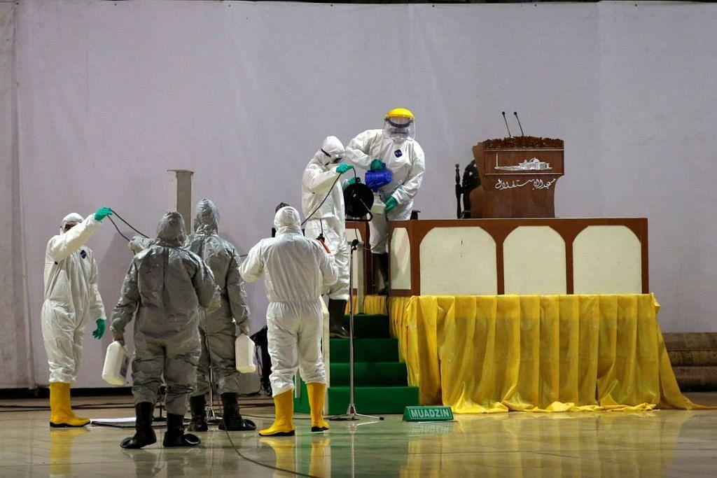LAKUKAN PEMBERSIHAN: Pegawai perubatan dan kebersihan sedang menyembur cecair nyah kuman di kawasan dalaman Masjid Istiqlal dalam usaha untuk mencegah penularan Covid-19. – Foto REUTERS