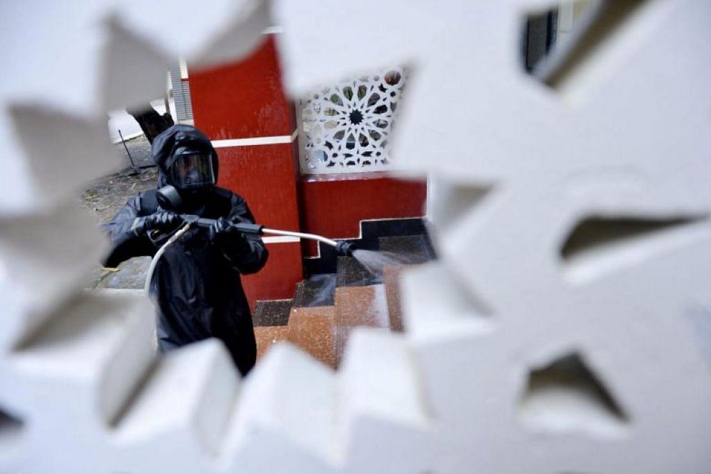 BASMI KUMAN: Seorang pegawai yang memakai sut perlindungan menyembur bahan basmi kuman di sebuah masjid di Makassar, Indonesia pada 16 Mac 2020.
