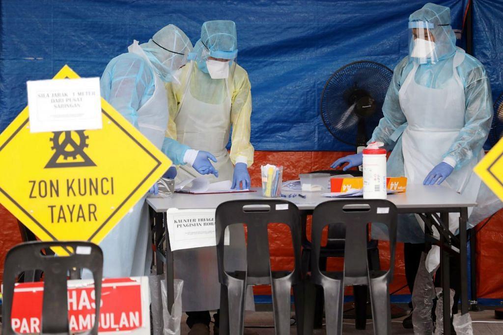 PEMERIKSAAN DIPERLUAS: Beberapa pekerja kesihatan dengan alat pelindung peribadi sedang bertugas di satu perkhemahan yang ditubuhkan sebagai pusat pemeriksaan di satu klinik di Kuala Lumpur pada 23 Mac 2020. - Foto REUTERS.