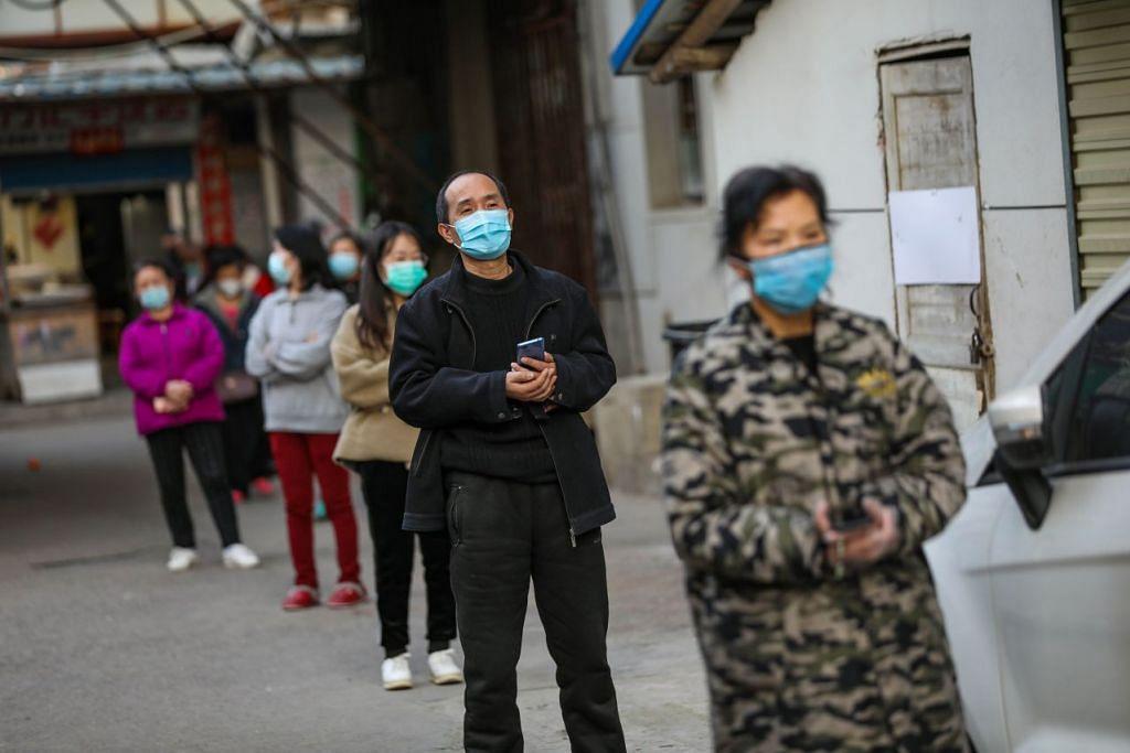 KEADAAN DI WUHAN: Beberapa penduduk Wuhan sedang beratur untuk makanan yang dihantar ke kediaman mereka sewaktu menjalani kuarantin pada 18 Mac 2020. - FOTO: AFP.
