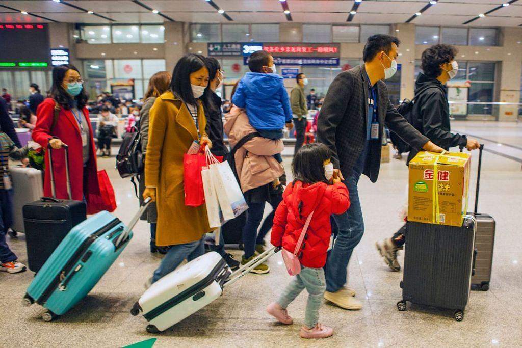 SEKATAN PERGERAKAN DITIADAKAN: Seorang pekerja asing bersama keluarganya dilihat sedang bergegas menuju ke keretapi yang akan berangkat ke Shenzhen, Yichang, Wilayah Hubei di China pada 23 Mac 2020. - FOTO: AFP